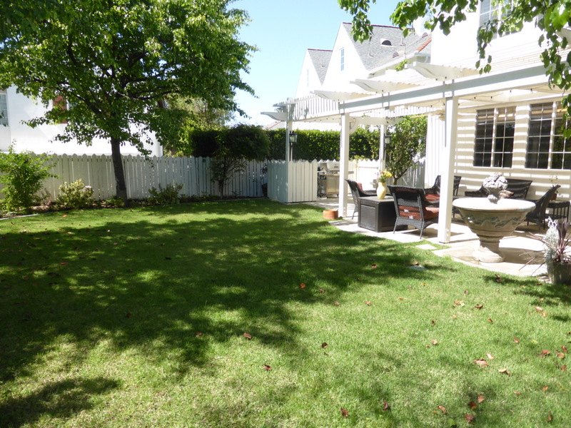 patio stretching the length of the yard and a big grassy area