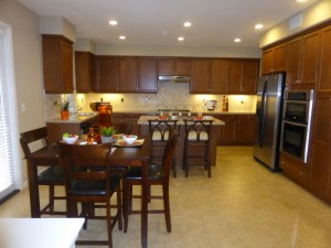 the rest of the kitchen features rich brown cabinetry and granite countertops the center island can comfortably seat two or three people one wall of the